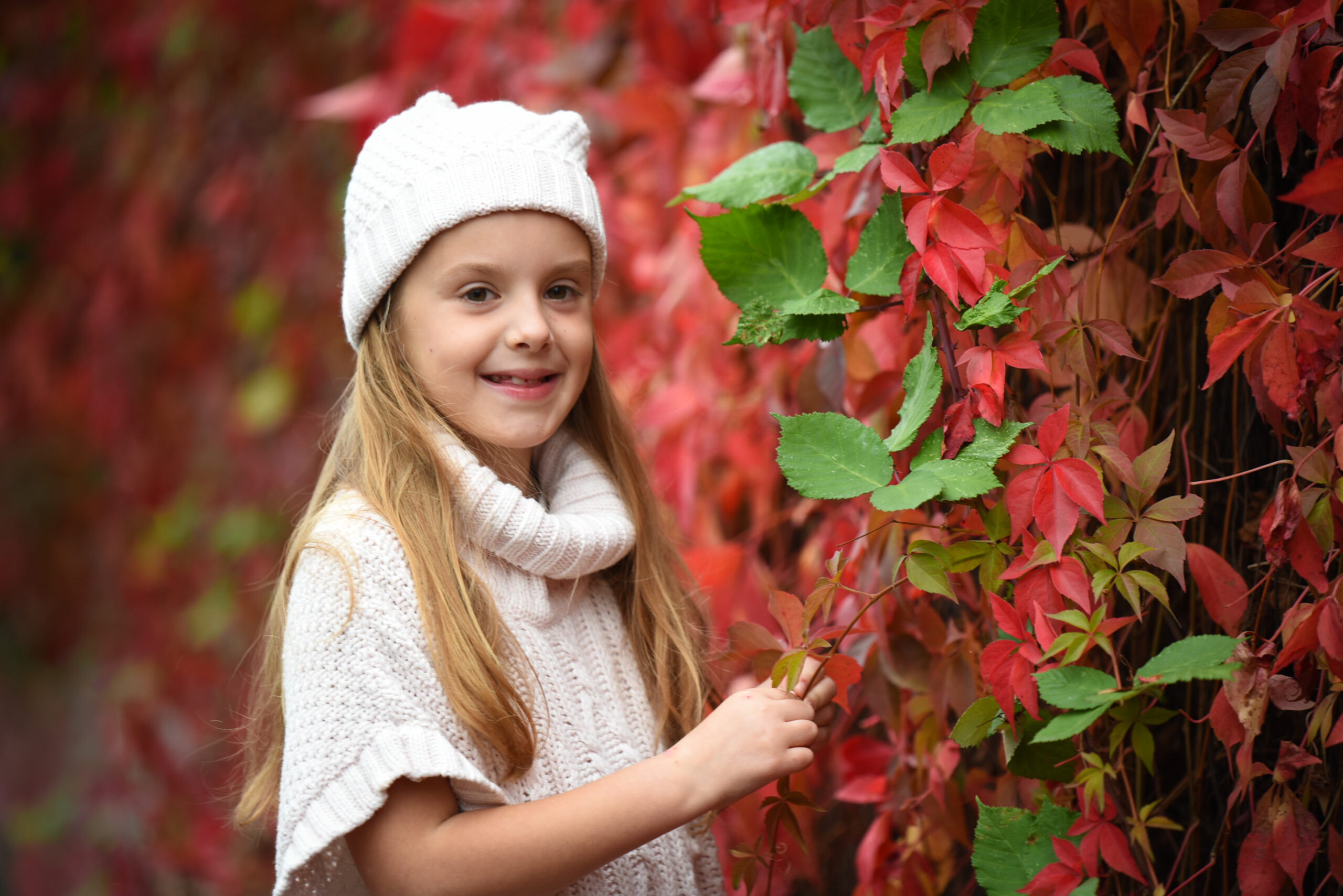 young girl in red autumn leaves