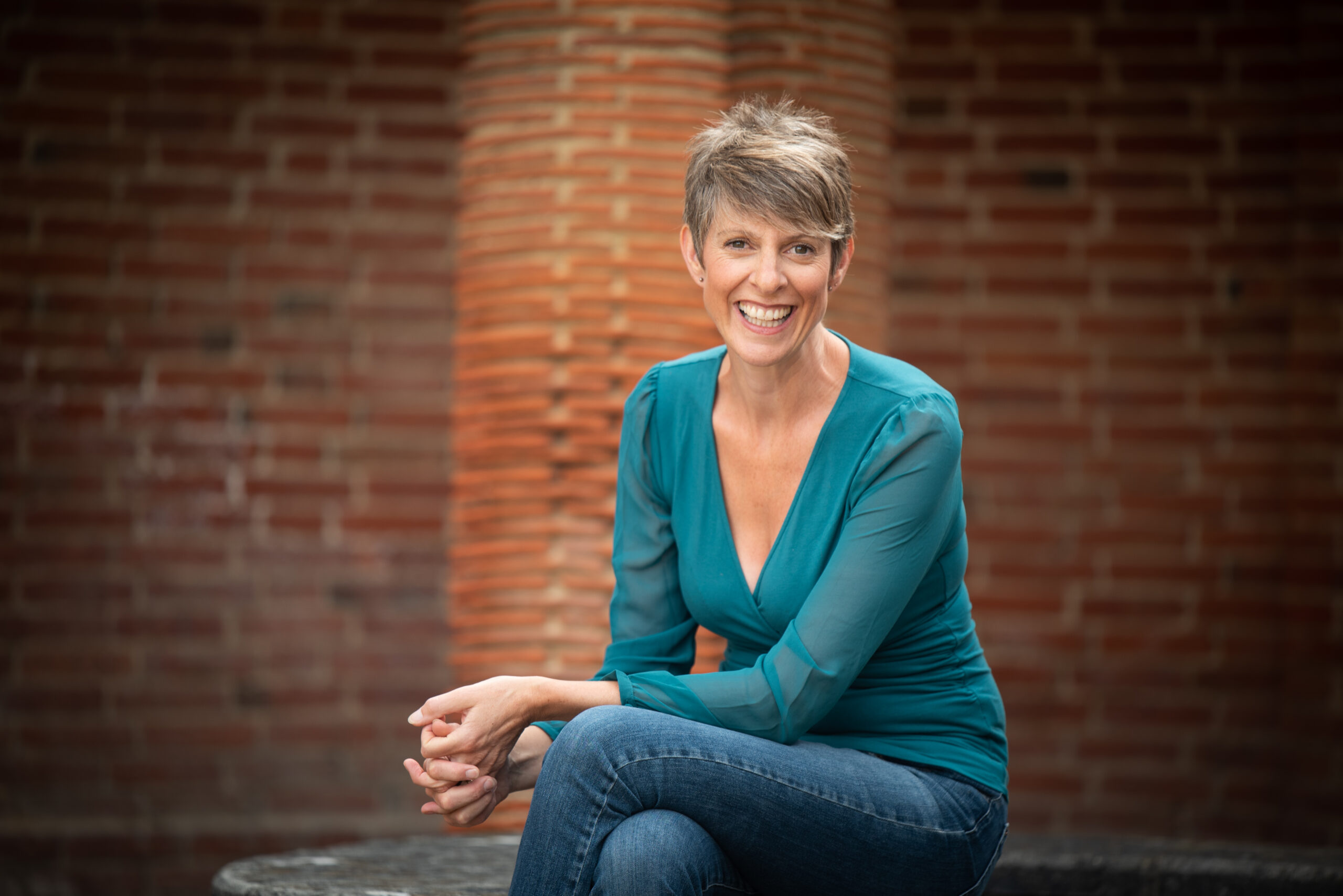 lady sitting with brick wall