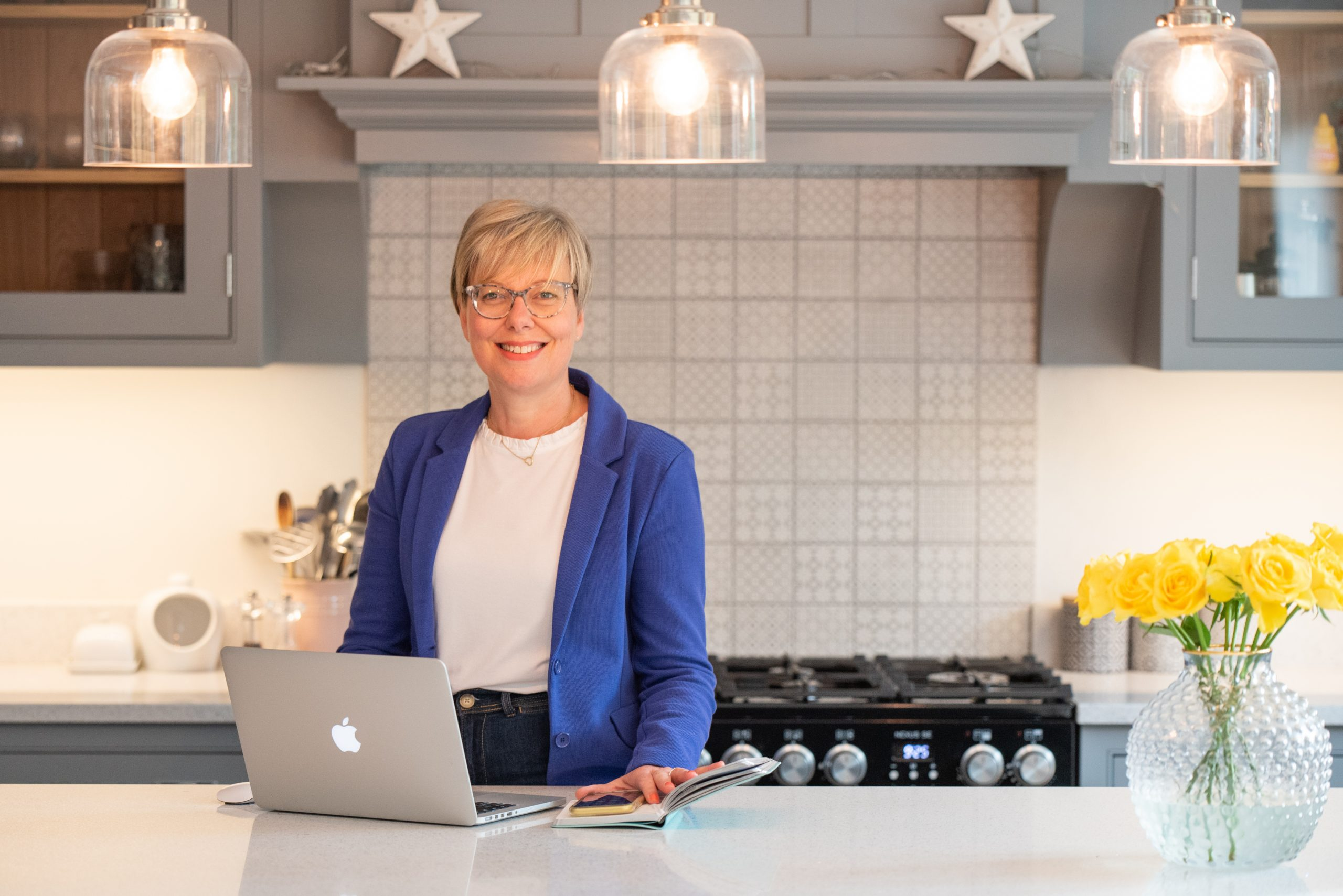blonde lady in kitchen with laptop
