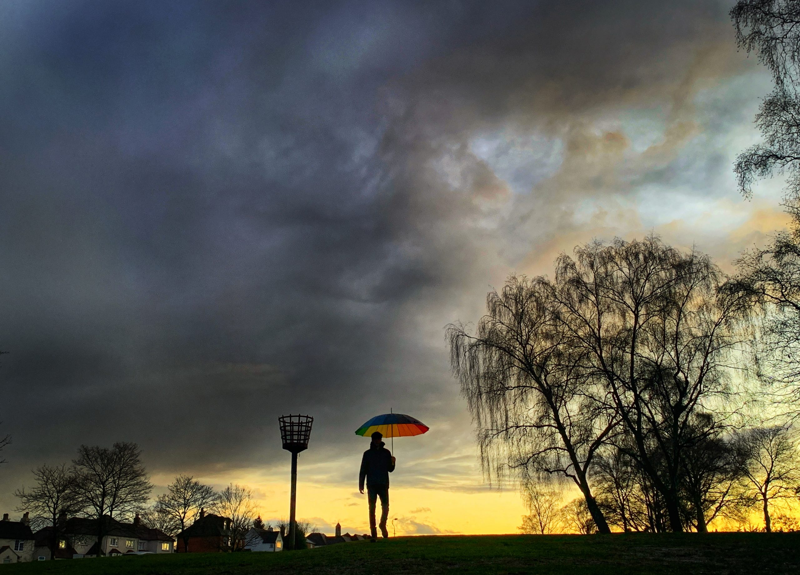 silhouette of man with umbrella in sunset